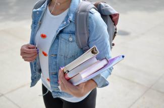 ragazza con zaino in spalla e libri in mano